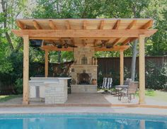Covered seating area with a stone fireplace and outdoor kitchen - Southwest Fence & Deck