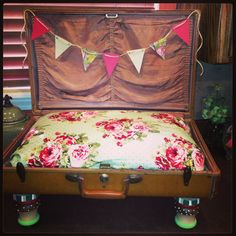 Made a dog bed out of a vintage Samsonite suitcase. Bought wooden furniture legs with brackets from Lowes, painted them! Got fabric and sewed over an old pillow. Made a pennant flag just for fun! Wa-la! Easy and Fun project! Cost=$27.00 for supplies (wooden foot pieces were $5 each)
