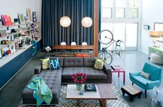 Like the globe pendant lights and the blue chair eclectic living room by Daleet Spector Design
