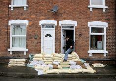 A man steps over sandbags outside his house on Alney Island.