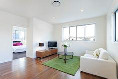 weiß gestrichene Wohnung mit Laminatboden, grüner Teppich, runder Designer-Couchtisch, weiße Couch