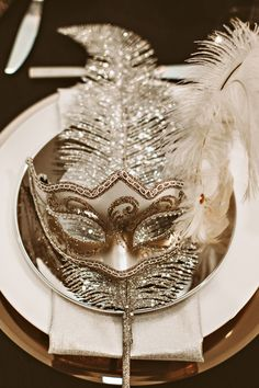 a mask at each table for a New Year's party, photo by Hazelwood Photo http://ruffledblog.com/black-and-gold-new-years-eve-wedding #weddingideas #newyearseve