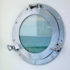 Using a Porthole Window as Picture Frame: http://www.completely-coastal.com/2016/02/porthole-window-picture-frame.html