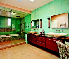 Tile in Totality: Tile is making its presence known in contemporary baths; occupying more wall, floor and backsplash space. Translucent recycled glass in a muted pine green for the tub deck were paired with small mosaic tiles in colors meant to evoke a tranquil sunset. Linen-textured, sand colored porcelain tile flooring presents the foundation for a restful space wrapped in glass tile. Design by Bonnie Bagley-Catlin, Jackson Design and Remodeling, San Diego, CA. Photo by Preview First.