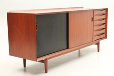 Low sideboard in teak with two reversable painted sliding doors. Designed by Arne Vodder and manufactured by Sibast Furniture, Fyn Denmark in the 1950s. www.reModern.dk