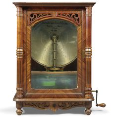 A LOCHMANN 21½-INCH DISC MUSICAL BOX, NO. 2656, GERMAN, CIRCA 1900 the coin operated movement plaining on two combs, the walnut veneered case with arched glazed door flanked by turned and fluted pilasters above a frieze coin drawer; together with twenty one discs