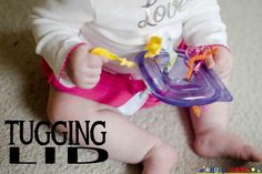 Create a simple tugging lid for baby to play with. Using a Tupperware lid and ribbon, baby has something to safely pull and chew at while playing.