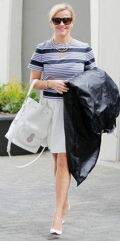 Reese Witherspoon in a striped shirt and a white skirt.