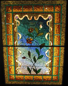 Flowers in a Ribbon Frame ~ Belcher Mosaic Glass Company, Newark, New Jersey ~ 1880s  The mosaic was created by sandwiching the glass pieces between two gummed asbestos sheet, pouring molten metal between the sheets to fill in the gaps and when cooled, removing the asbestos sheets.