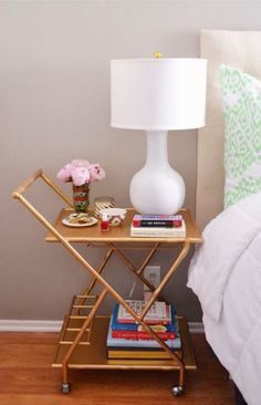 A gold bar cart makes a charming and creative bedside table.