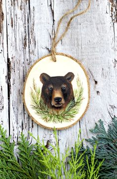 *Artist Made*  Original, hand painted illustration of a forest-dwelling grizzly bear with paw to reverse.  Dimensions Height: 8.9cm Width: 7.9cm Depth: 0.5cm  This listing is for the exact wooden ornament shown. It is a unique item and would make a very thoughtful gift. Please see the front and back view of the ornament. This double sided design allows for the ornament to spin and hang gracefully, this way all angles of the ornament can be appreciated. This design channels the ever-beautiful…