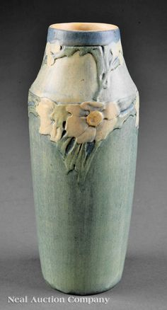 A Newcomb College Art Pottery Semi-Matte Glaze Vase, 1913, decorated by Sadie Irvine in a relief-carved camellia motif, blue, green and yellow underglaze, base marked with Newcomb cipher, decorator's mark, shape no. 6, and reg. no. FW5, height 8 in