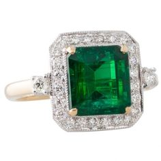 f7f63afcbcdf2d yellow and white gold ring with a GIA certified square cut Brazilian emerald  in four yellow gold claws above a surround of grain set diamonds with mill  ...