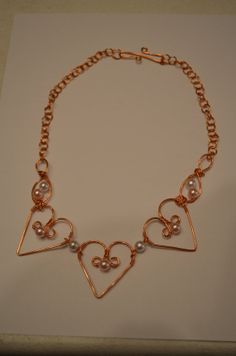 Handcrafted Maiden's Blush Copper Heart Necklace / Handmade Copper Chain / Valentines Day / Wire Wrapped / Beads / Spirals $15         These are pieces of jewelry made from real copper, glass beads, handmade chains that we handcraft ourselves. You can find us at www.facebook.com/worldofspearcraft   and our shop is at www.etsy.com/shop/spearcraft