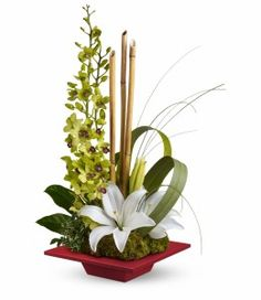 Secret Oasis - This lovely, serene bouquet makes a Zen-sational gift for any special occasion with an artistic arrangement of orchids, lilies and exotic accents in a red bamboo dish.