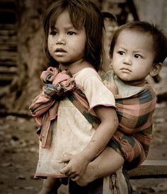 Laotian girl carrying toddler, by David Leach -- National Geographic Your Shot