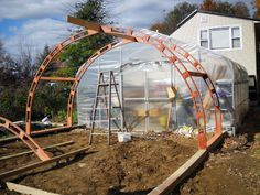 Try this easy method to build your own greenhouse using laminated wooden arches that you can make yourself and extend your growing season on the homestead.