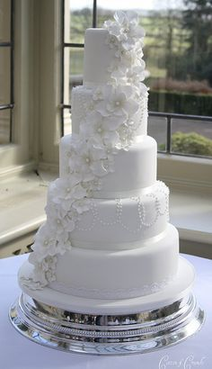 Bright white wedding cake with sugar flowers and royal icing.