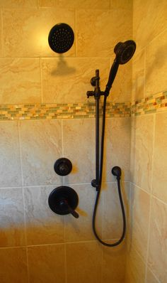 Delta Lahara shower trim in oil rubbed bronze with hand held unit on a slide bar.