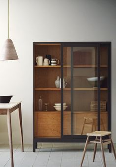 The Joyce cabinet, by Russell Pinch, is inspired by Victorian optometrist's shop-fitting. It has sliding glass fronted doors and a cherry-lined interior with multiple shelves and drawers, making it suitable for a variety of uses throughout the house.