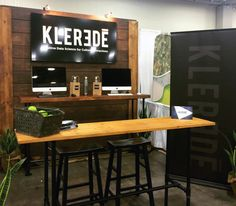 Klerede tradeshow booth. Reclaimed wood and pipe tables functional, rustic and easy to take down after the show. Wooden backdrop, easy to setup and take down.