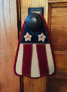A touch of Americana designed by Oley Valley Primitives. This door hanger measures 10 by 7 inches, and fit on every door handle I tried. Penny Rug Patterns, Wool Applique Patterns, Doorknob Hangers, Door Hangers, Door Hanger Template, Primitive Quilts, Felted Wool Crafts, Wool Embroidery, Penny Rugs