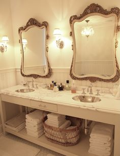 French master bath design with white custom double bathroom vanity with beveled marble countertop, metal hammered double sinks, chair rail & beadboard, white porcelain hexagon tiles floor and gilt mirrors.