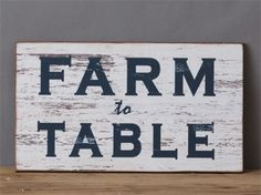 """We are in love with this large, distressed """"Farm to Table"""" wall sign! Featuring rustic, faux peeling paint with the graphics """"Farm To Table"""" in bold dark navy letters!  Perfectly sized to make a statement in your kitchen space! We love pairing this charming sign with a small boxwood wreath!   Wall sign includes two carved eye-holes on back for easy hanging.   Made of: MDF / Wood Dimensions: 10.25"""" H x 18"""" W  SHIPPING NOTICE:  THIS ITEM LEAVES OUR WAREHOUSE WITHIN FIVE DAYS."""