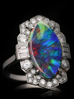 An Art Deco platinum, black opal and diamond ring, circa 1935. Marked platinum, and numbered.