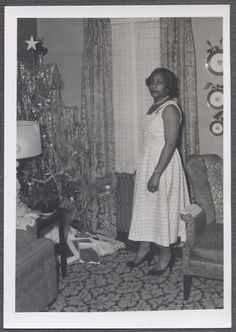 (Was just talking to my Mom about how our family would get dressed up for every major holiday Christmas, Thanksgiving and Easter) Vintage Christmas photo of African American woman posing next to decorated tree full of presents.