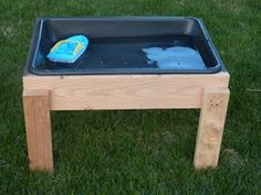"""DIY Water Table: """"The project cost us under $11.00 to complete. We used wood leftover from the previous home owners found in our basement. If you don't have any scrap wood you could ask at a construction site if you could take some of their extra pieces. The plastic tub is a cement mixing tub from Home Depot and was about $5.50. They had two different sizes in stock and we choose the smaller tub. I used leftover stain from my deck to protect the table from the elements."""""""