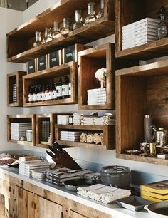 In the kitchen area, reclaimed-wood boxes display Paltrow's cookbooks, Staub ceramic cookware, and carafes from Nussbaumer's Milagro Collection.