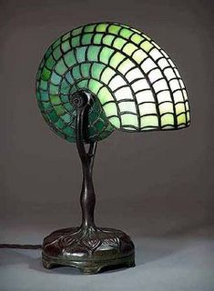 Nautilus lamp, a Tiffany lamp. The first Tiffany lamp was created in part of the Art Nouveau movement. Originally designed by Clara Driscoll, not Louis TIffany (as believed previous to Beautiful, intricate, and whimsical.