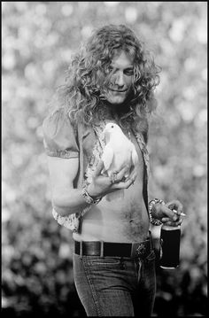 Robert Plant, Led Zeppelin, holding a dove while drinking a beer and smoking. Legendary work by rock photographer Neal Preston.