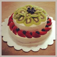 Yellow chiffon cake with whipped cream icing, decorated with strawberries, kiwi and blueberries.