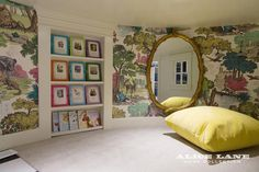 Round playroom features walls clad in Cole & Son Folie Versailles Grand Wallpaper fitted with a recessed floor to ceiling bookcase next to a floor to ceiling gold faux bois mirror and a yellow floor cushion.