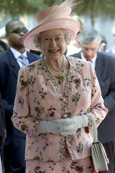 Queen Elizabeth, in Pale Pink two piece suit with embroidered dark red cherries. Matching Hat with an Egret feather .