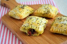 Panini bladerdeeghapjes (voor 12 hapjes) •6 plakjes bladerdeeg •4 plakjes parmaham •1 bol mozzarella •groene pesto •zongedroogde tomaatjes •1 ei, geklutst •Italiaanse kruiden