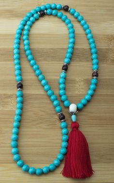 This high quality handcrafted full length meditation mala beads necklace features Turquoise Magnesite with Rosewood intervals, pewter accents and a bone guru bead as well as a 100% cotton red color ta