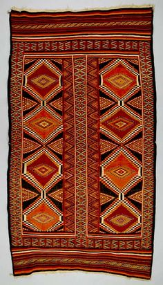 Africa | Floor rug from Redeyef, Tunisia | ca. early to mid 20th century | Wool; weft-faced, weft-float, interlocking tapestry woven | Rug production in northwestern Tunisia started in the early 20th century when immigrants from Libya settled in this region. Sharp, dynamic geometric designs woven in the warm colours of the desert and mountains, and dramatic composition of stripes and diamonds in weft-float and interlocking tapestry, are exclusively characteristic of rugs from Redeyef.