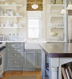 Gray blue kitchen cabinets with marble countertops, gray blue kitchen island with butcher block countertop, farmhouse sink, schoolhouse pend...