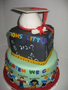 Graduation cake with little sugar paste children ringing the bottom tier, one for each child in the class.