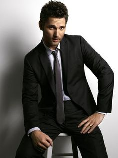 Simple black suit with grey skinny tie, subtly blue shirt. Ft. Eric Bana.