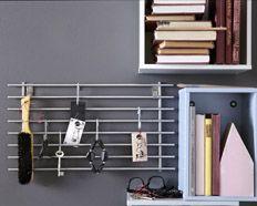 Creëer een handig ophangrek door een Ikea LÄMPLIG pannenrek aan de muur te bevestigen. Gebruik BYGEL haakjes om er sleutels en andere belangrijke snuisterijen aan op te hangen.