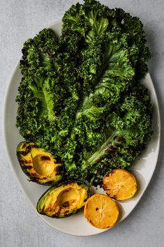 This grilled kale salad is paired with avocado, lemon, garlic, toasted pecans, and parmesan. Grilling kale makes it SO flavourful and a little crispy – it's one of my favourite salad recipes to date! #kale #salad #healthyrecipe