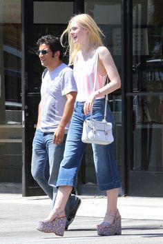 Elle Fanning tries her Solid & Striped swimsuit on dry land, adding this season's must-have denim culottes and sky-high wedges.