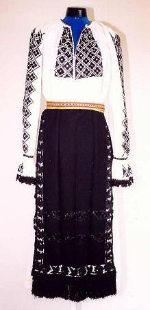 Romanian Women's costume from county of Făgăraş  Gathered neck linen blouse (cămaşă încreţită), with gathered cuffs with small frill. It is decorated with blocks of black geometric  embroidered motifs on the front, and sleeves. The neck has an edging with a narrow row of black embroidery and a row of black crochet lace is attached to the cuff frills. Black velvet waistcoat  (ilic)