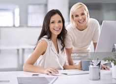 Two businesswomen conferring with one another on a project