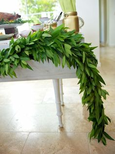A dramatic garland made of lush greenery is an inexpensive way to transform the look of your buffet. This one was created by connecting bay laurel branches with floral wire, then fastening it to the corners of the table for an organic, seasonal pop of color. Bay laurel can be ordered from any wholesale florist
