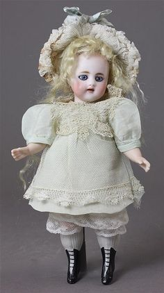 """7 1/2"""" SIMON & HALBIG #886 ALL BISQUE CHILD ~ SOCKET HEAD MARKED AS SHOWN, MOHAIR WIG, STATIONARY GLASS EYES, OPEN MOUTH WITH 2 UPPER SQUARE CUT TEETH. 5-PIECE CHUNKY BODY AND PAINTED/MOLDED BOOTS/STOCKINGS. CHIP ON LEFT HIP, FAINT HAIRLINE FROM RIM TO NECK. VERY NICELY DRESSED."""